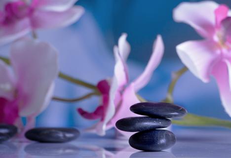 Massagesteine auf spiegelnder Fläche mit Orchideen im Hintergrund